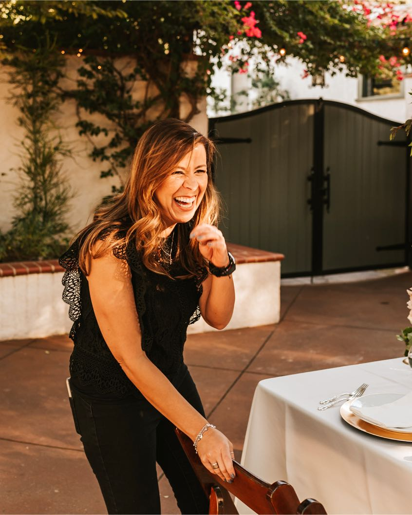 Wedding planner Karla Solorzano smiling next to a table