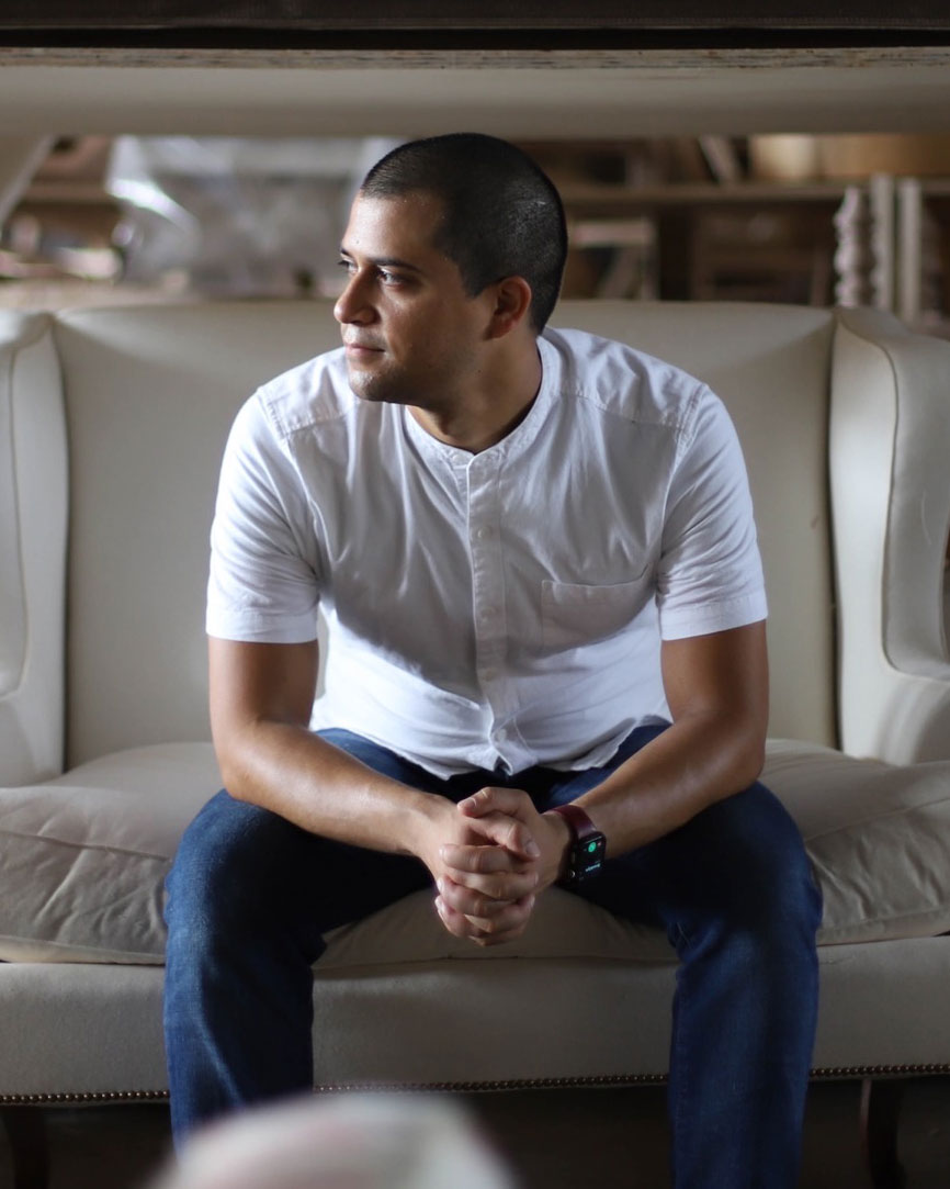 Founder of Luther Quintana upholstery Luther Quintana Jr. sitting on a cream-colored couch