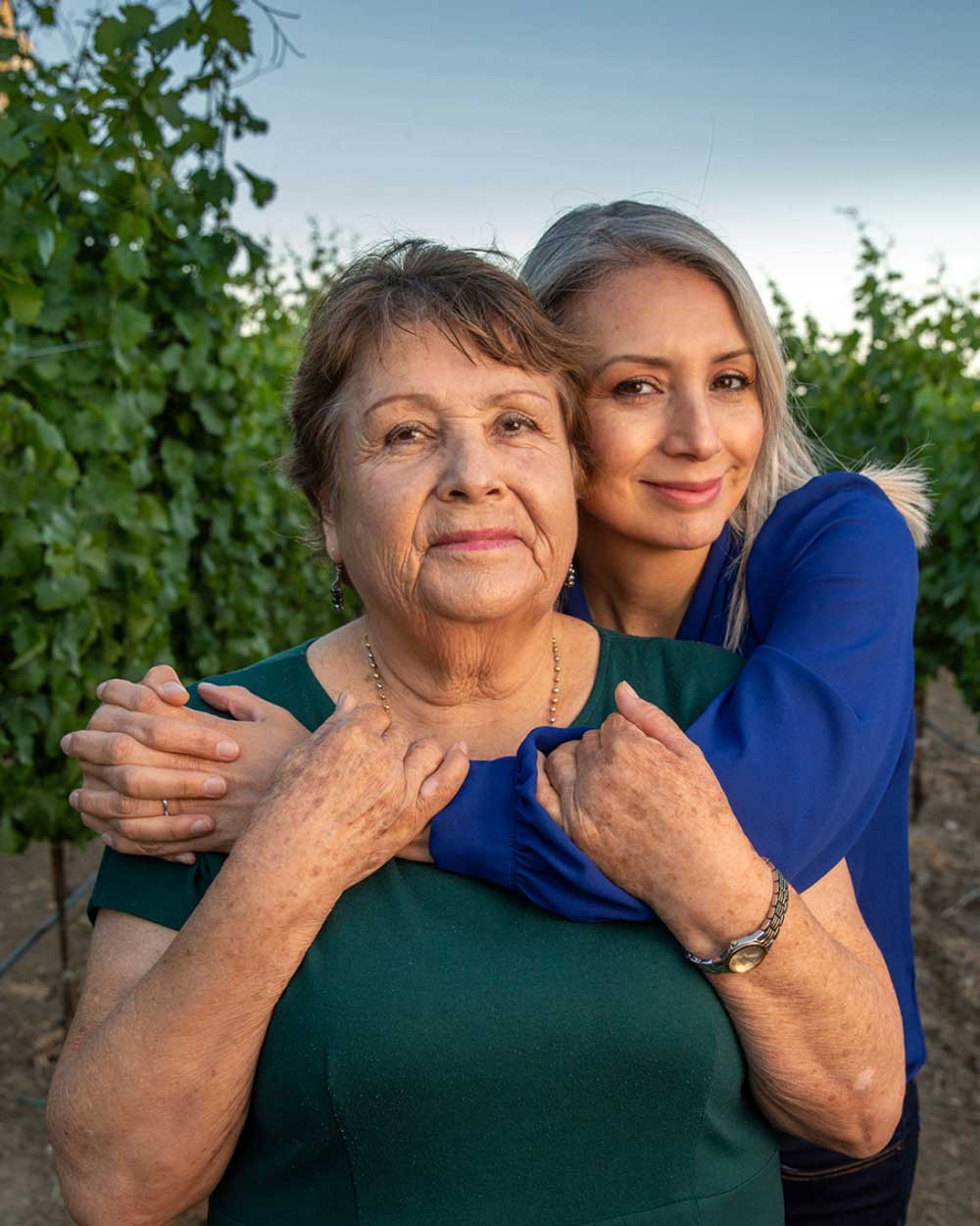 Co-owner of Robledo Family Winery Maria Robledo being hugged by her daughter Vanessa in a vineyard