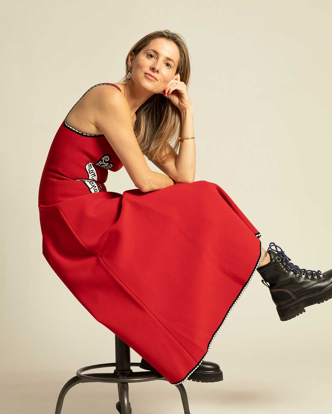 Founder of Larroudé Marina Larroudé sitting on a stool in a red dress and black boots