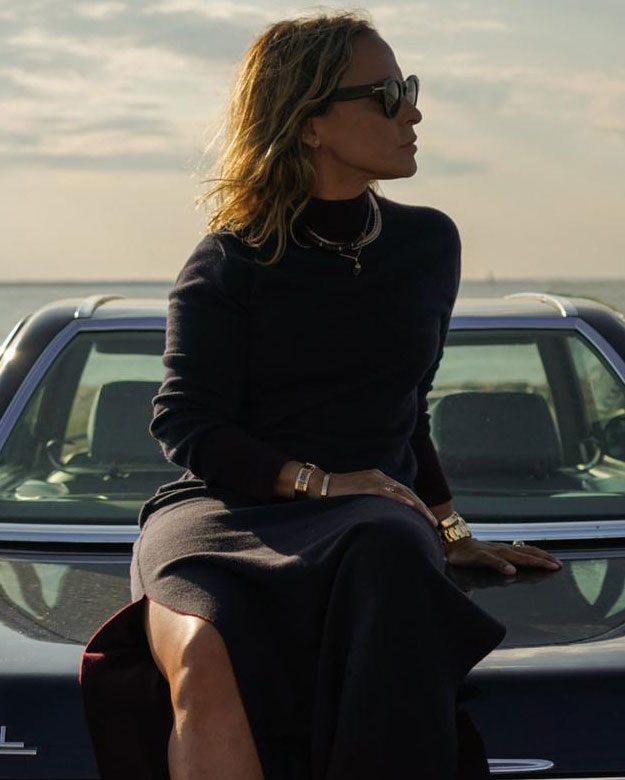 Jewelry designer Sara Beltrán sitting on a car in a black dress and sunglasses